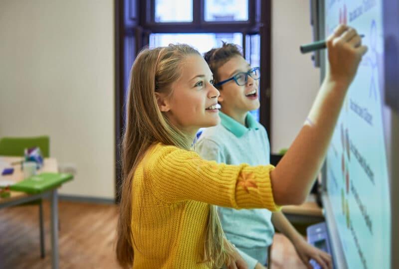 Deux enfants qui écrivent au tableau