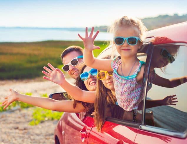 Famille saluant par la fenêtre d'une voiture