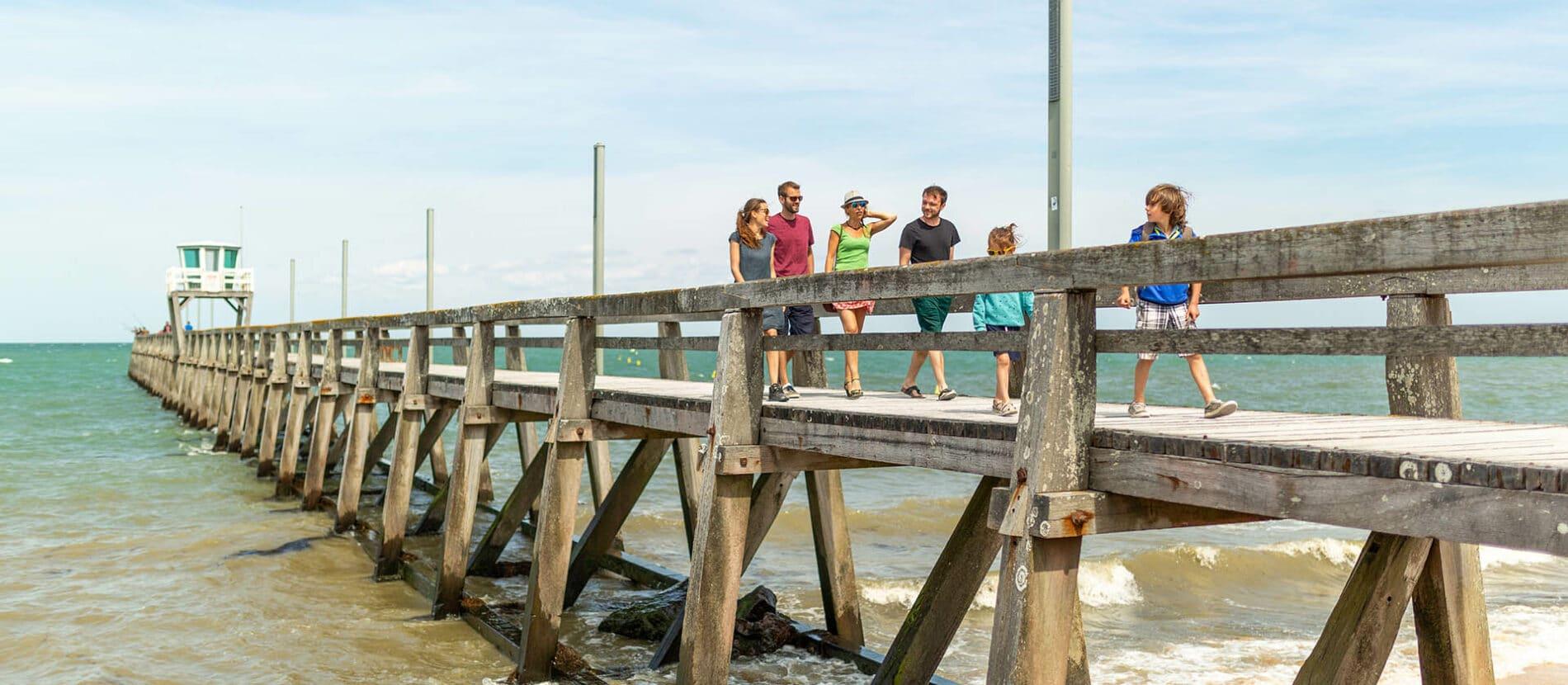 Une famille en balade sur le ponton au dessus de la mer à Luc-sur-mer