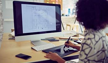 Femme travaillant un plan d'architecte sur son ordinateur