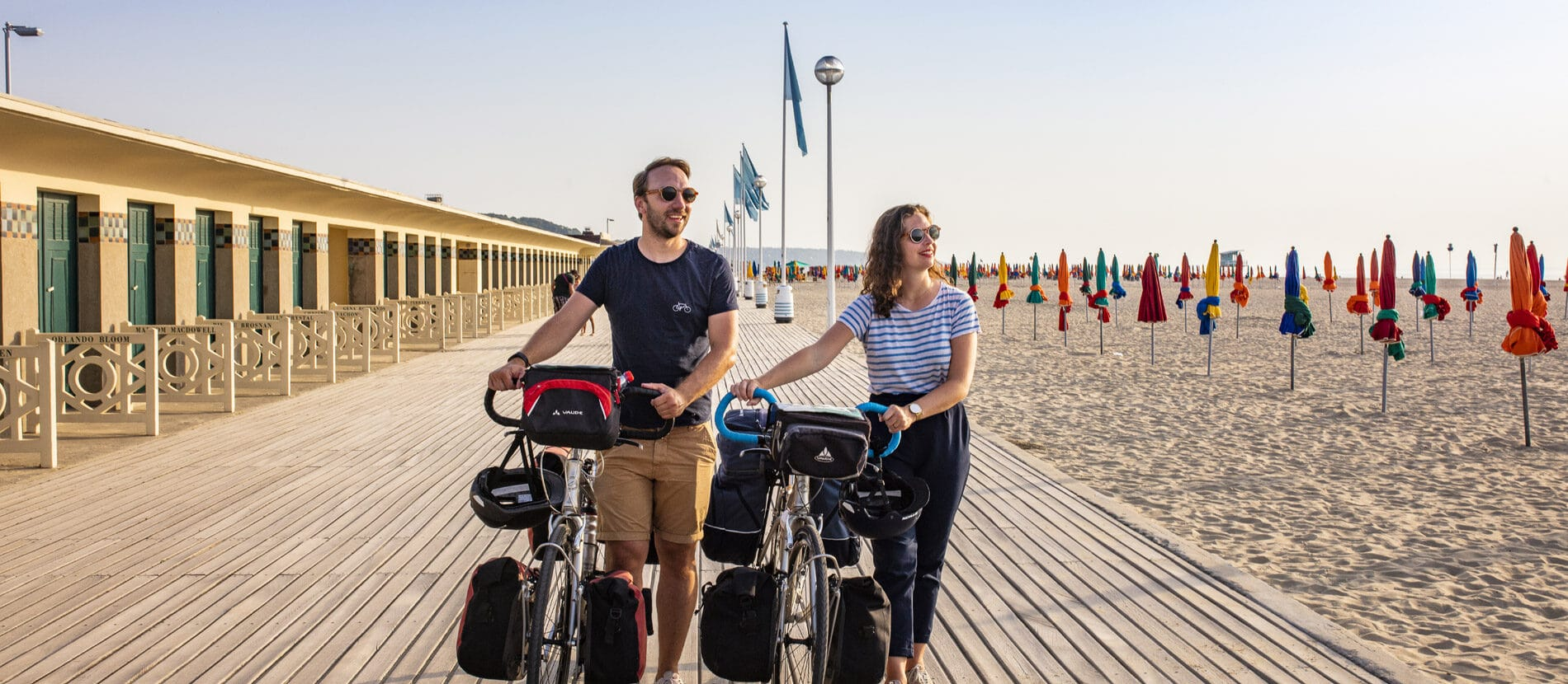 Couple en balade à vélo sur les planches de Deauville