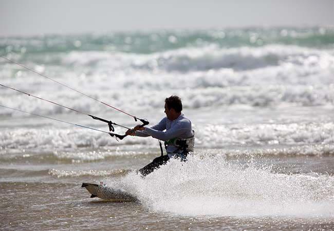 Homme pratiquant du kite surf en mer