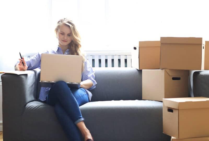 Femme dans son canapé entourée de cartons