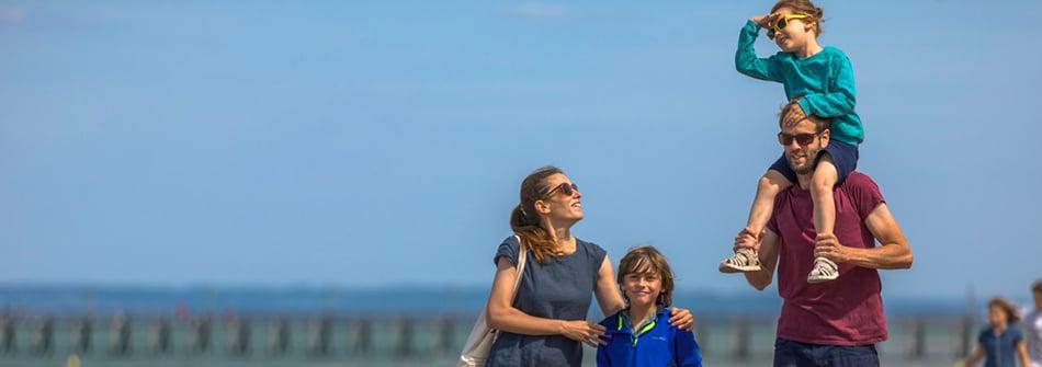 Balade en famille sur la digue le long de la plage