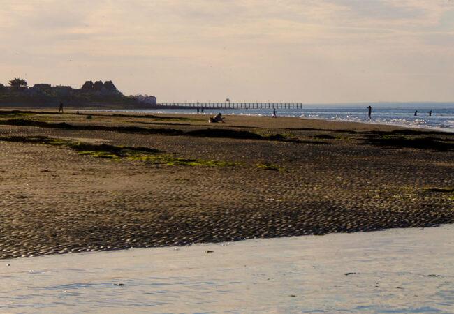Coucher de soleil sur la plage de Lion sur Mer dans le Calvados avec des personnes qui marchent dans l'eau