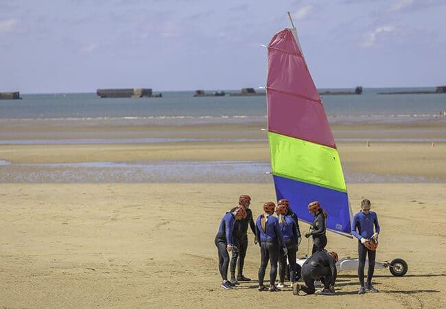 Baptême de char à voile pour un groupe d'hommes et femmes sur une plage du Calvados