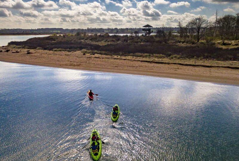 Kayaks bi-places et simple en train de naviguer dans la Baie de l'Orne avec vue sur l'observatoire de la Pointe du Siège