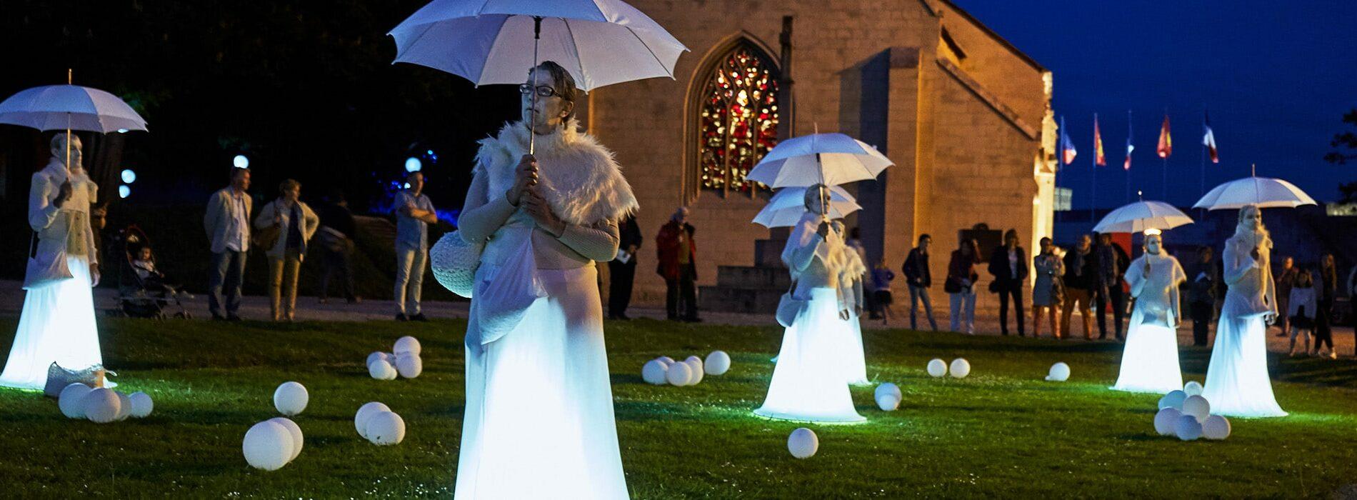 Femme déguisée en blanc avec des parapluies